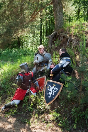 Knights in armour resting under the tree at forest photo