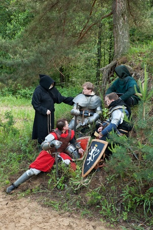 Knights in armour resting under the trees at forest photo