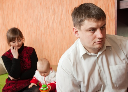 young marriage quarreling at home. Their baby sitting between them photo