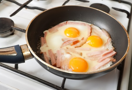 eggs and bacon on hot skillet.