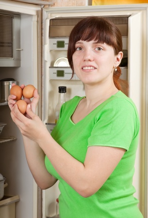 Young woman putting fresh eggs into fridge at home photo