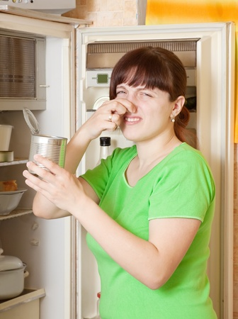 woman  holding her nose because of bad smell near fridge at home photo