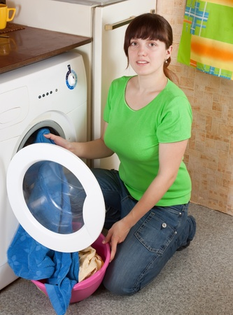 Young woman loading the washing machine in kitchen photo