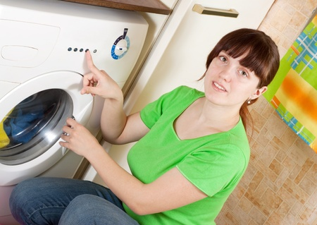 Young woman doing laundry with washing machine at her home photo