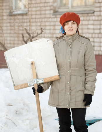 young woman with shovel in snowy street photo