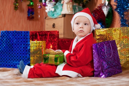 自宅のクリスマス プレゼントとサンタ クロースのような服を着て少年