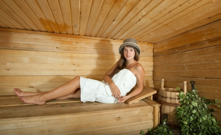 stive: Dressed woman lying  on wooden bench in sauna