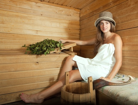 stive: girl in white sheet sits on  bench in a sauna Stock Photo