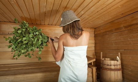 girl is steamed in the sauna with birch flag broom photo