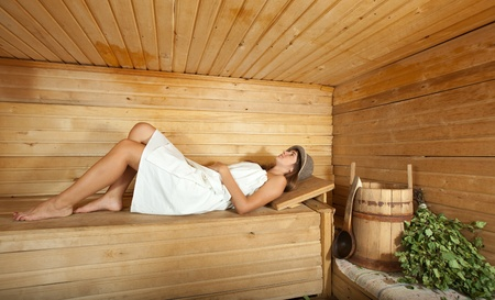 swelter: Young woman is taking a steam-bath  in sauna