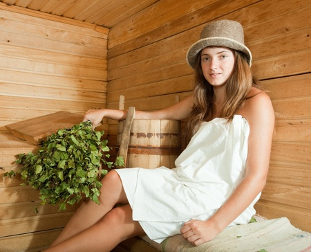 finnish bath: Young girl relaxing on wooden bench in sauna   Stock Photo