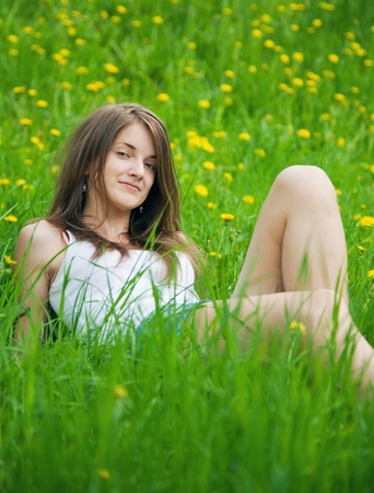 long-haired teen girl lying from meadow grass photo