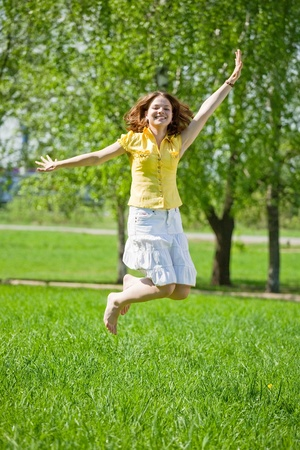 Jumping girl in yellow against summer meadow Stock Photo - 10533593