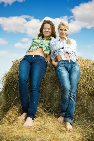 Young girls standing on top of hay bail photo
