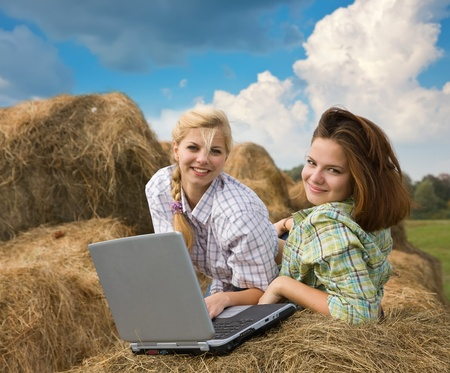 country girls resting with laptop on fresh hay bale photo