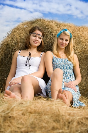 Pretty girls in dresses resting on hay bale photo