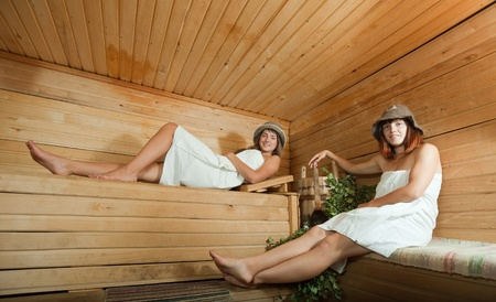 stive: Happy girl sitting on wooden bench in sauna