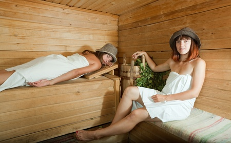 bathhouse: Young girls relaxing on wooden bench in sauna  Stock Photo