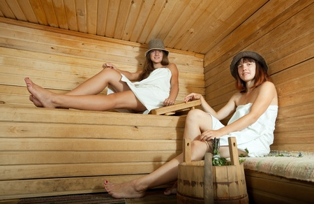 russian hat: Two young women taking steam at sauna Stock Photo