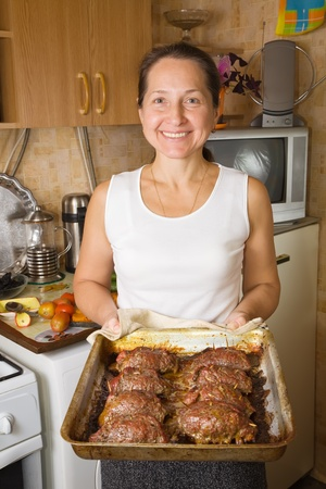cook griddle: Mature woman with cooked stuffed beef on cook griddle in kitchen. One of the stages of preparation of  stuffed beef.  See series Stock Photo