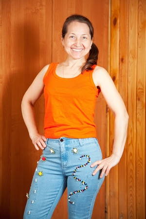 Mature woman  shows a handmade jeans beaded by herself Stock Photo - 10557937