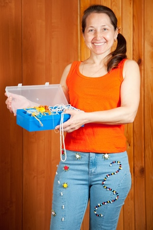 stitchwork: Mature woman  shows a handmade jeans beaded by herself Stock Photo