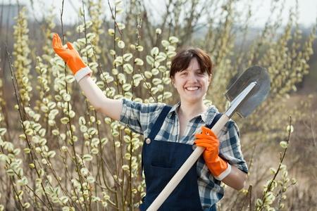 welcom: Female farmer with spade gesturing welcom