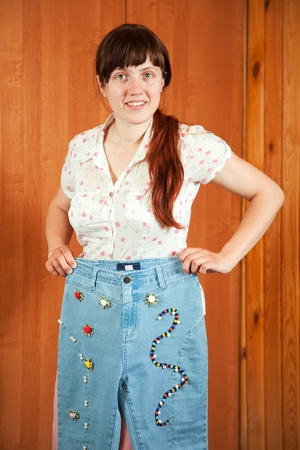 Woman shows a handmade jeans beaded by herself Stock Photo - 10606355