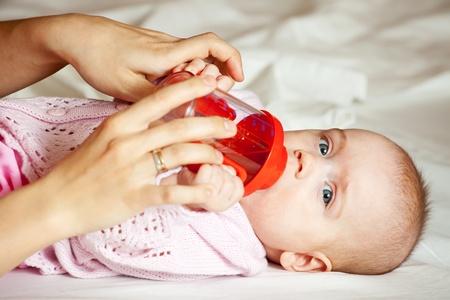 babygro: Feeding procedure of little baby girl on white sheet Stock Photo