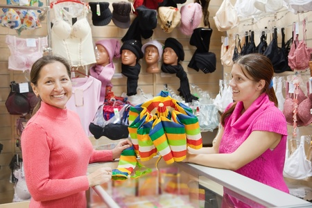 pays: Saleswoman and customer with purchases at  counter in underwear shop Stock Photo