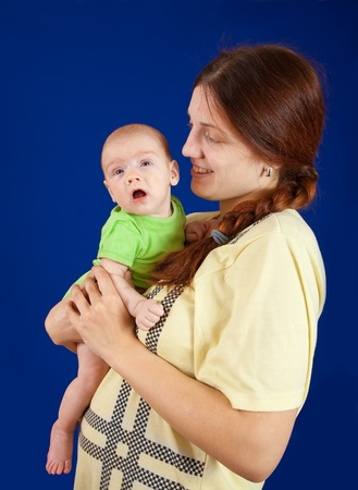 3 month: Mother holding  3 month baby on blue background.