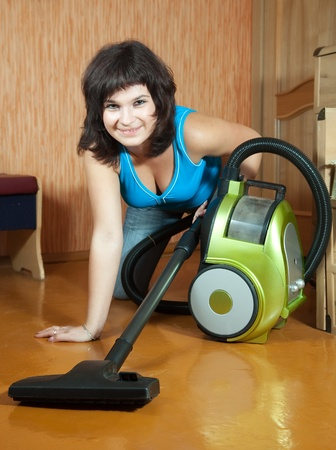 girl cleans with vacuum cleaner at home photo