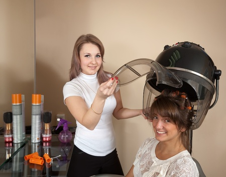 saloon: Female hairdresser working with hair dryer