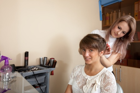 haircutting: Female hair stylist working with long-haired girl. Focus on customer Stock Photo