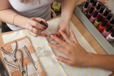 nailcare: manicurist working with  woman nails