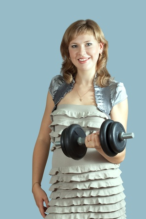 casualy: Young woman in dress exercising with barbell