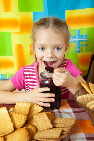 Little girl eating marmalade from  glass jar at kitchen Stock Photo - 10677831