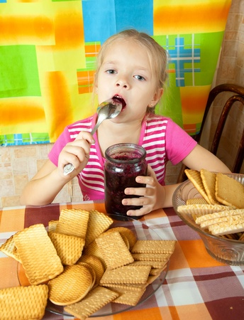 Little girl eating jam from  jar at kitchen Stock Photo - 10677830