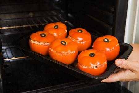 farci: Closeup of cook hands putting stuffed tomato into oven. See in series stages of cooking of farci tomato