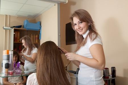 hairtician: hair stylist work on woman hair in salon