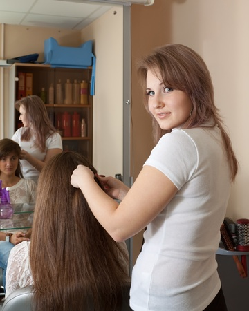 hair stylist work on woman hair in salon photo