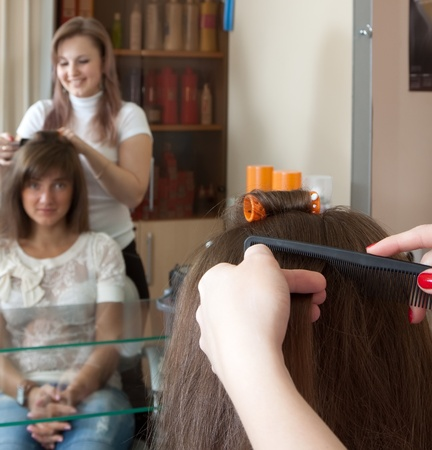 Female hair stylist working with long-haired girl Stock Photo - 10704888