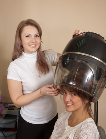 hairtician: Female hairdresser working with hair dryer