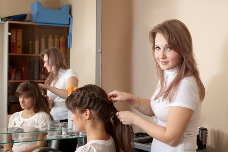 Female hair stylist working with long-haired girl photo