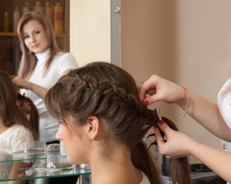 Female hairdresser working with long-haired girl photo