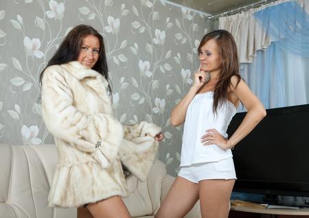 furskin: Woman  make boast of fur coat  in home Stock Photo