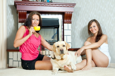 woman only: Two mid adult women with  labrador retriever in home interior. Focus on  left woman only