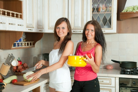Two mid adult women cooking at them kitchen photo