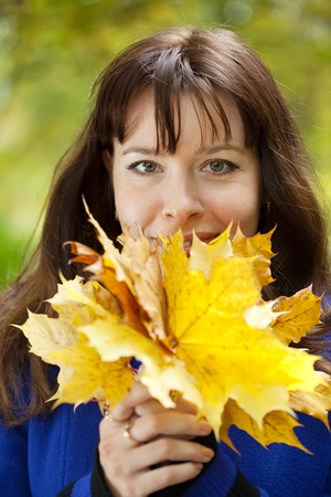 Outdoor portrait of happy woman in autumn with maple posy photo