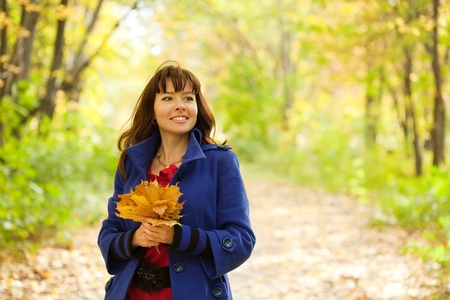 Outdoor portrait of   woman with maple posy photo